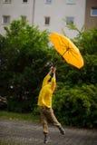 一件明亮的黄色雨衣的小家伙在手中飞行在与伞的地球 免版税库存图片