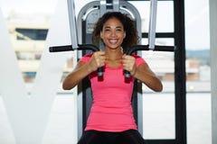 一件明亮的T恤杉的女孩做在胸肌的体育锻炼 库存照片