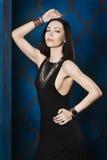 一件黑晚礼服和豪华金黄首饰的华美的深色头发的妇女 免版税图库摄影