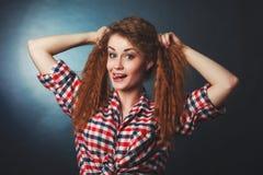 一件格子花呢上衣的一个逗人喜爱的红发女孩在演播室 免版税库存图片