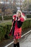 一件桃红色夹克的妇女在城市附近走 图库摄影