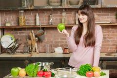 一件桃红色夹克的深色的妇女在厨房里站立在与新鲜蔬菜的一张桌附近并且拿着一个绿色苹果 库存照片