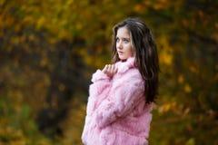 一件桃红色皮大衣的美丽的女孩 免版税库存照片