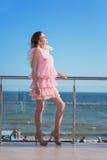 一件桃红色礼服的一位可爱和美丽的女性在一个晴朗的旅馆` s阳台摆在 豪华的生活方式 免版税库存图片