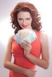 一件桃红色礼服的一名美丽的妇女有欧洲钞票的在手上 免版税库存照片