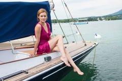 一件桃红色礼服的可爱的妇女在一条美丽的游艇 库存图片