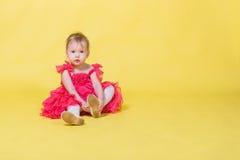 一件桃红色礼服的女孩小孩在穿在他的脚的黄色背景鞋子 库存照片