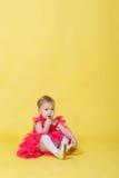 一件桃红色礼服的女孩小孩在穿在他的脚的黄色背景鞋子 免版税库存照片