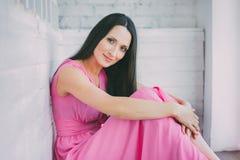 一件桃红色礼服的妇女坐倾斜在木白色墙壁 他看照相机和微笑 库存照片