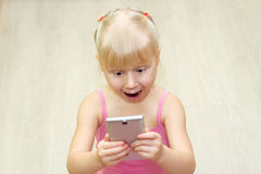 一件桃红色礼服的小女孩惊吓了与手机 免版税库存照片
