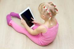 一件桃红色礼服的小女孩按一个片剂屏幕 库存图片