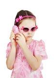 一件桃红色礼服的小女孩谈话由玩具电话 免版税库存照片