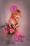 一件桃红色礼服的白肤金发的女孩有在她的头发的一朵花的 免版税库存图片