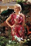 一件桃红色礼服的白肤金发的女孩有花的 免版税库存照片