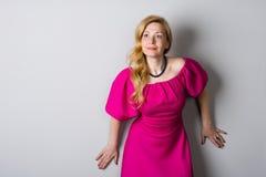 一件桃红色礼服的美丽的妇女在墙壁附近 免版税图库摄影