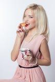 一件桃红色礼服的美丽的时兴的快乐的女孩在一个减速火箭的样式用新月形面包和一杯茶在一白色背景isola的 图库摄影