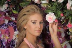 一件桃红色礼服的美丽的金发碧眼的女人在庭院里 免版税库存图片