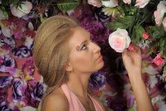 一件桃红色礼服的美丽的金发碧眼的女人在庭院里 库存图片