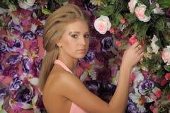 一件桃红色礼服的美丽的金发碧眼的女人在庭院里 图库摄影