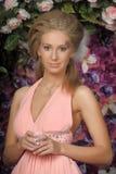 一件桃红色礼服的美丽的金发碧眼的女人在庭院里 免版税库存照片