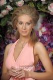 一件桃红色礼服的美丽的金发碧眼的女人在庭院里 库存照片
