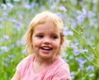 一件桃红色礼服的逗人喜爱的小女孩微笑在公园的 免版税图库摄影