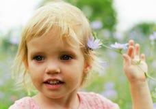 一件桃红色礼服的逗人喜爱的小女孩微笑在公园的 免版税库存照片