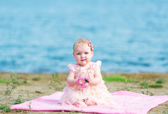 一件桃红色礼服的婴孩坐河岸 库存图片