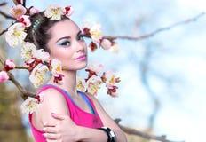 一件桃红色衬衣的女孩有春天的开花 免版税库存照片