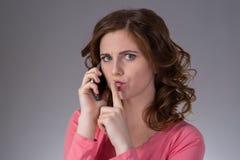 一件桃红色衬衣的美丽的少妇表现出与s的情感 免版税图库摄影