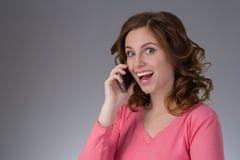 一件桃红色衬衣的美丽的少妇表现出与s的情感 免版税库存图片