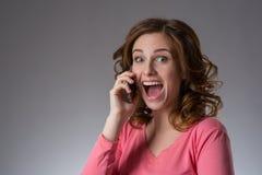 一件桃红色衬衣的美丽的少妇表现出与s的情感 免版税库存照片
