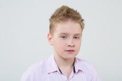 一件桃红色衬衣的镇静男孩有被翻动的头发的 库存图片