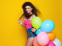 一件桃红色衬衣的年轻和美丽的卷曲女孩和在举行五颜六色的气球和笑的黄色背景的蓝色短裤 图库摄影