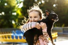一件桃红色镶边女衬衫的女孩拿着在胳膊的一条狗 库存照片