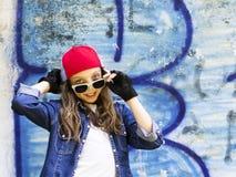 一件棒球帽和牛仔布衬衣的逗人喜爱的年轻金发女孩少年在石墙背景 库存照片