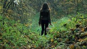 一件棕色夹克的苗条少妇走通过森林的拿着篮子 库存图片