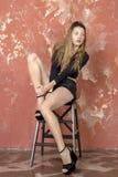 一件黑毛线衣和皮革短裤和平台凉鞋的年轻长发长腿的皮包骨头的女孩 库存照片