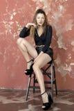 一件黑毛线衣和皮革短裤和平台凉鞋的年轻长发长腿的皮包骨头的女孩 免版税库存照片