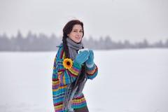 一件毛线衣的美丽的女孩在与一杯茶的冬天步行 库存照片