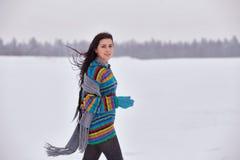 一件毛线衣的美丽的女孩在冬天步行 免版税库存图片