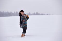 一件毛线衣的美丽的女孩在冬天步行 免版税库存照片