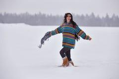 一件毛线衣的美丽的女孩在冬天步行 库存照片