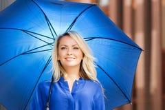 一件海军衬衣的美丽的少妇有一把蓝色伞的 免版税库存图片