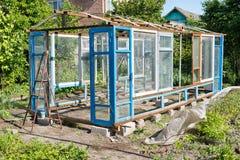 一间温室的建筑在从小块材料的庭院里 图库摄影