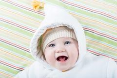 一件温暖的夹克的愉快的笑的婴孩有一个滑稽的帽子的 免版税图库摄影