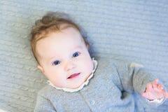 一件温暖的被编织的毛线衣的甜女婴在缆绳编织毯子 免版税库存图片