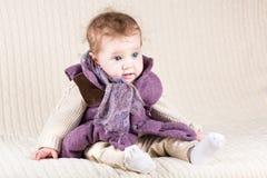 一件温暖的紫色夹克的滑稽的女婴 免版税库存图片