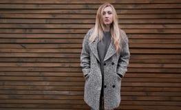一件灰色外套的年轻美丽的白肤金发的女孩 库存照片