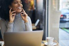 一件灰色夹克的卷曲非裔美国人使用与快速的互联网的无线连接在咖啡馆wifi区域 免版税库存图片